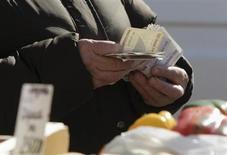 Уличный торговец на осенней ярмарке в Минске считает рубли 29 сентября 2012 года. Национальный банк Белоруссии снизит ставку рефинансирования до 28,5 с 30 процентов с 13 марта в связи с замедлением инфляции в феврале и прогнозом дальнейшего сокращения темпа роста потребительских цен, говорится в сообщении Нацбанка. REUTERS/Vasily Fedosenko