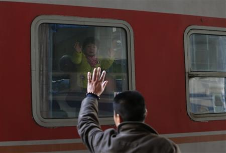 A child waves to his father from a train as it leaves from Hangzhou railway station in Hangzhou, Zhejiang province January 26, 2013. REUTERS/William Hong