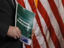 Член Бюджетного комитета Палаты представителей США держит копию предложений для достижения сбалансированного бюджета, составленных Республиканской партией, во время пресс-конференции в Вашингтоне 12 марта 2013 года. Обещание президента США Барака Обамы положить конец бюджетным войнам в Вашингтоне натолкнулось на препятствие во вторник, когда республиканцы и демократы Конгресса предложили абсолютно разные планы сокращения дефицита. REUTERS/Gary Cameron