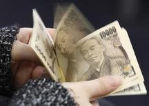 Женщина считает иены в Токио 28 февраля 2013 года. Распродажа иены остановилась в среду, но ожидания радикального смягчения политики Банка Японии означают продолжение слабости японской валюты. REUTERS/Shohei Miyano