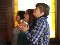 Stephanie Gillett (R) and her partner Cassey Gillett (C), pray during a Sunday morning church service at the Open Door Community Fellowship Church in Louisville, Kentucky, March 2, 2013. In Louisville, an activist and a minister represent the dueling factions of the Bible Belt's nascent gay rights movement. Photo taken March 2, 2013. REUTERS/John Sommers II