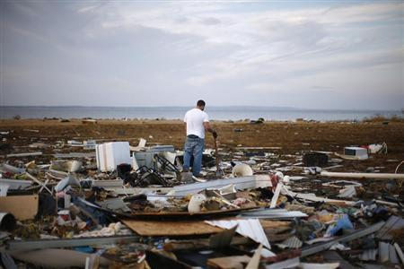 A resident looks through a house that was destroyed by Hurricane Sandy is seen in Union Beach, New Jersey November 12, 2012. REUTERS/Eric Thayer