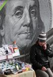 Лоток в центре Киева на фоне плаката с изображением американской банкноты 19 ноября 2012 года. США от имени сотни стран призвали Украину оставить попытки пересмотреть согласованные с ВТО импортные пошлины, предупредив, что это может вызвать цепную реакцию и погрузить мировую торговлю в хаос. REUTERS/Anatolii Stepanov