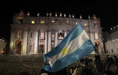 Faithful wave Argentina's flag after white smoke rose from the chimney above the Sistine Chapel, indicating a new pope has been elected at the Vatican, March 13, 2013. REUTERS/Giampiero Sposito