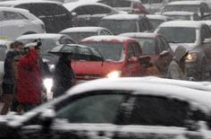 Люди проходят мимо автомобилей во время снегопада в Киеве 3 декабря 2012 года. Украина вводит дополнительные пошлины на импорт легковых автомобилей с объемом двигателя от 1.000 до 2.200 кубических сантиметров на срок три года, чтобы защитить отечественных производителей, находящихся на грани остановки. REUTERS/Anatolii Stepanov