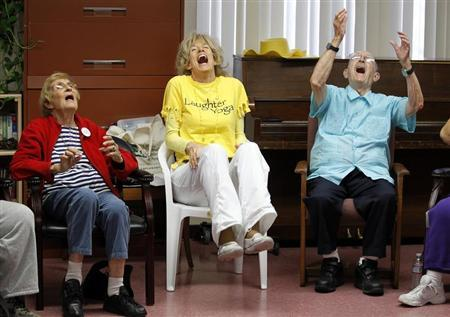 Dr. Funshine, aka Caroline Meeks, M.D. (C) leads a laughter therapy session with Wanda Boyce (L) and Richard Trask along with a group of seniors at the Clairmont Friendship Center in San Diego, California November 17, 2010. REUTERS/Mike Blake
