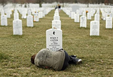 Lesleigh Coyer, 25, of Saginaw, Michigan, lies down in front of the grave of her brother, Ryan Coyer, who served with the U.S. Army in both Iraq and Afghanistan, at Arlington National Cemetery in Virginia in this March 11, 2013, file photo. Coyer died of complications from an injury sustained in Afghanistan. REUTERS/Kevin Lamarque/Files UNREST OBITUARY)