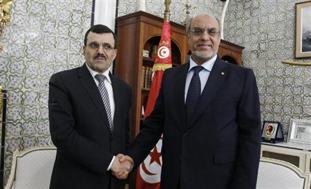 Tunisia's Prime Minister Ali Larayedh (L) shakes hands with former Prime Minister Hamadi Jebali at the government palace in Tunis March 14, 2013. REUTERS/Zoubeir Souissi