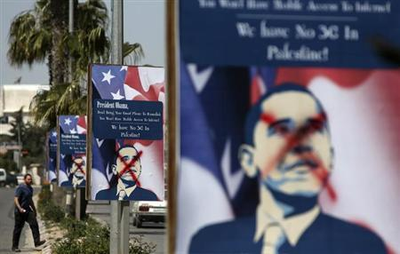 A Palestinian man walks near defaced placards depicting U.S. President Barack Obama, ahead of his visit to the region, in the West Bank city of Ramallah March 14, 2013. REUTERS/Mohamad Torokman