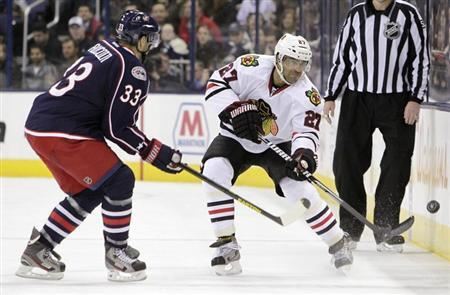 Chicago Blackhawks' Johnny Oduya (27) clears the puck as Columbus Blue Jackets' Adrian Aucoin (33) defends during their NHL hockey game in Columbus, Ohio, March 14, 2013. REUTERS/Jay LaPrete