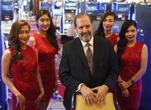Solaire Casino-Resort Chief Operating officer Michael French (C) poses with waitresses a few days before the casino opening in Pasay city, Metro Manila March 14, 2013. REUTERS/Erik De Castro