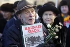 A man holds a placard during the annual procession commemorating the Latvian Waffen-SS (Schutzstaffel) unit, also known as the Legionnaires, in Riga March 16, 2013. REUTERS/Ints Kalnins