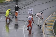 Equipe de apoio da F1 retira excesso de água da pista antes de treino classificatório do Grande Prêmio da Austrália, no circuito de Albert Park, em Melbourne. 16/03/2013 REUTERS/Daniel Munoz