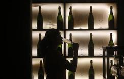 A woman poses with a glass of wine at a tapas bar in Mumbai March 9, 2013. REUTERS/Vivek Prakash