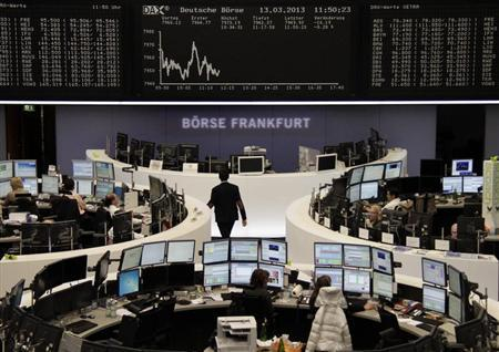Traders work at their desks in front of the DAX board at the Frankfurt stock exchange March 13, 2013. REUTERS/Remote/Lizza David
