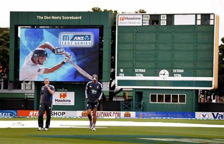 England's captain Alastair Cook (R) walks off the ground with team coach Andy Flower after inspecting the pitch during a rain delay on the final day of the second cricket test against New Zealand at the Basin Reserve in Wellington March 18, 2013. REUTERS/David Gray