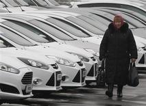 Женщина шагает мимо автомобилей на стоянке автодилера в Киеве 14 марта 2013 года. Евросоюз призвал Украину, рассчитывающую до конца года подписать с ним соглашение о зоне свободной торговли, отказаться от намерения ввести заградительные пошлины на импорт легковых автомобилей, наносящие ущерб европейской экономике. REUTERS/Sergii Polezhaka