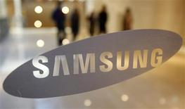 Un grupo de visitantes camina detrás del logo de Samsung Electronics Co en su casa matriz en Seúl, ene 7 2010. Samsung Electronics Co está desarrollando un dispositivo digital portátil similar a un reloj pulsera, dijo una fuente en contacto con el tema, con lo que se suma a su rival Apple en la creación de nuevos productos en momentos en que el crecimiento de las ventas de celulares de alta gama se está desacelerando. REUTERS/Jo Yong-Hak