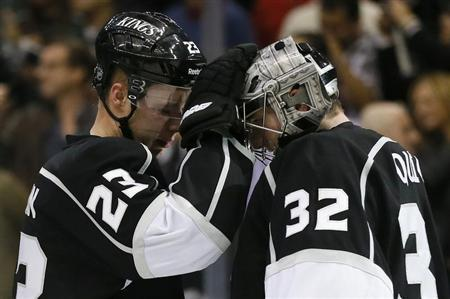 Los Angeles Kings captain Dustin Brown (L) celebrates with teammate goaltender Jonathan Quick after they defeated the Calgary Flames during their NHL hockey game in Los Angeles, March 11, 2013. REUTERS/Lucy Nicholson