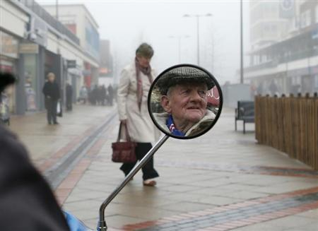 A pensioner talks to a friend (unseen) while sitting on a mobility scooter in Corporation Street in Corby, central England November 15, 2012. REUTERS/Eddie Keogh