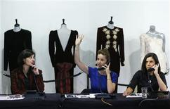 A worker takes telephone bids during the auction of ten dresses worn by Britain's Princess Diana, at Kerry Taylor Auctions in London March 19, 2013. REUTERS/Andrew Winning