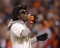 """Rapper Lil Wayne sings """"Take Me Out To The Ball Game"""" during the seventh inning stretch in Game 6 of the MLB NLCS playoff baseball series between the St. Louis Cardinals and the San Francisco Giants in San Francisco, October 21, 2012. REUTERS/Robert Galbraith"""