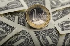 Монета в 1 евро лежит на долларовых купюрах в Варшаве, 18 января 2011 года. Евро близок к четырехмесячному минимуму, так как отказ Кипра от налогообложения банковских вкладов вызывает неуверенность в финансовом будущем страны и стабильности еврозоны. REUTERS/Kacper Pempel