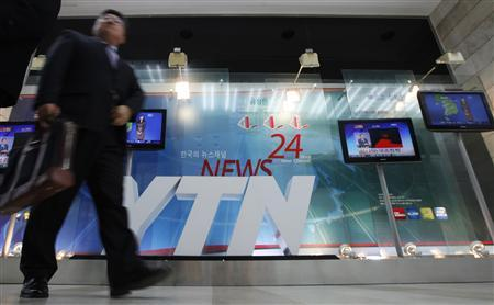 A man walks at the main office of television network YTN in Seoul March 20, 2013. REUTERS-Lee Jae-Won