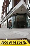 Человек проходит мимо дорожного знака, упавшего рядом с офисом Bank of Cyprus UK в центре Лондона 18 марта 2013 года. ФРС США, скорее всего, продолжит ежемесячную скупку облигаций на сумму $85 миллиардов, несмотря на улучшение экономических данных, поскольку новая вспышка кризиса в еврозоне напомнила регуляторам о неспокойной мировой обстановке. REUTERS/Andrew Winning