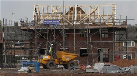 A worker drives a dumper truck past a house being built on a construction site in Chester, northern England March 20, 2013. REUTERS/Phil Noble