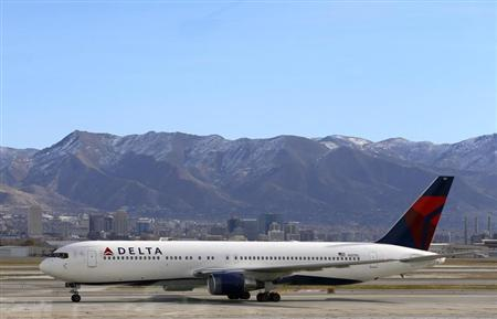 A Delta Airlines Boeing 767 passenger jet taxis past the Salt Lake City skyline, a day before the annual Thanksgiving Day holiday, at the Salt Lake City international airport, November 21, 2012. REUTERS/George Frey