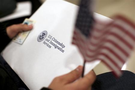A man holds a U.S. flag while receiving his proof of U.S. citizenship during a ceremony in San Francisco, California January 30, 2013. REUTERS/Robert Galbraith