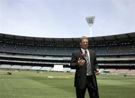 Australia's Shane Warne tosses a cricket ball as he stands on the turf of the Melbourne Cricket Ground after announcing his retirement from the sport at a news conference in Melbourne December 21, 2006. REUTERS/Stringer/Files