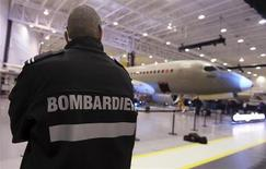 A security guard looks on as Bombardier unveiled its CSeries aircraft at a news conference at its assembly facility in Mirabel, Quebec, March 7, 2013. REUTERS/Christinne Muschi