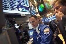 Трейдеры работают в торговом заде биржи NYSE в Нью-Йорке, 20 декабря 2012 года. Американские акции снизились в четверг из-за опасений по поводу Кипра и слабой отчетности Oracle. REUTERS/Andrew Kelly