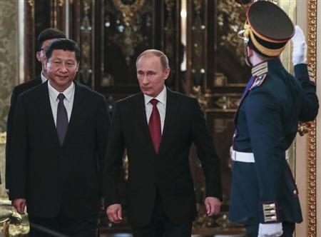 Russia's President Vladimir Putin (C) and his Chinese counterpart Xi Jinping walk into a hall as they meet at the Kremlin in Moscow March 22, 2013. REUTERS/Sergei Ilnitsky/Pool