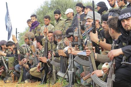 Free Syrian Army fighters carry their weapons as they sit in attention during the declaration of the formation of Al-Liwaa brigade in Binnish in Idlib province March 21, 2013. REUTERS-Mohamed Kaddoor-Shaam News Network-Handout