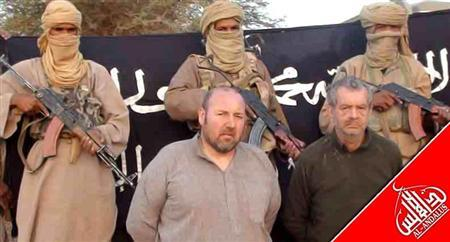 French nationals Philippe Verdon and Serge Lazarevic, who are being held hostage by Al Qaeda, are seen surrounded by masked men holding guns in an undisclosed location in Mali, in this undated handout picture. REUTERS/Agence Nouakchott Informations/Handout