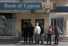 Люди пытаются снять деньги в банкомате около офиса Bank of Cyprus в Никосии, 21 марта 2013 года. Вкладчики Bank of Cyprus готовятся потерять 30 процентов депозитов, равных и превышающих 100.000 евро, сказал председатель финансового комитета кипрского парламента. REUTERS/Yorgos Karahalis (CYPRUS - Tags: POLITICS BUSINESS) - RTR3F9B8