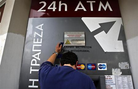 A man makes a transaction at an ATM outside a branch of Laiki Bank in Nicosia March 21, 2013. REUTERS/Yannis Behrakis