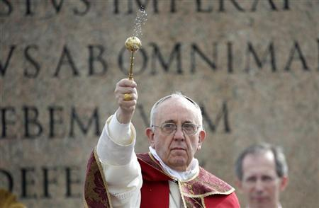 Pope Francis sprinkles holy water with an aspergillum as a blessing during the Palm Sunday mass at Saint Peter's Square at the Vatican March 24, 2013. REUTERS/Max Rossi