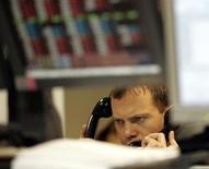 """Российский трейдер говорит по телефонам во время торгов на фондовой бирже в Москве 15 декабря 2004 года. Продажи акций сталеваров и ТНК-BP, которая даст """"материнской"""" компании почти $10 миллиардов, вызвали цепную реакцию на российском фондовом рынке, опустив индексы до минимальных отметок с ноября 2012 года. REUTERS/Alexander Natruskin"""