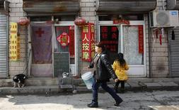 Pedestrians walk past a shop (L) providing Chinese dermatologic treatment at a street market on the outskirts of Beijing March 20, 2013. REUTERS/Kim Kyung-Hoon