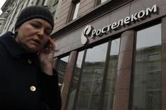 Женщина говорит по телефону, проходя мимо офиса Ростелекома в Москве 21 ноября 2012 года. Кремль решил назначить бывшего гендиректора Национальных кабельных сетей Сергея Калугина главой Ростелекома, сказал пресс-секретарь президента РФ Владимира Путина. REUTERS/Maxim Shemetov