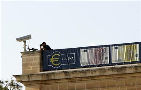 A police sniper stands guard on the roof of the Central Bank of Malta as a large consignment of Euro bank notes is delivered in Valletta October 31, 2007. REUTERS/Darrin Zammit Lupi