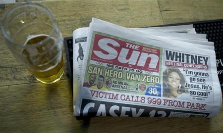 A copy of the Sun newspaper is seen next to a pint of beer in a pub in east London February 16, 2012. REUTERS/Olivia Harris
