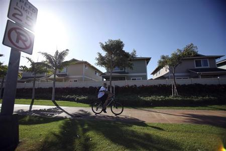 A man cycles past the Trades housing division built by Gentry Homes in Ewa Beach, Hawaii March 6, 2013. REUTERS/Hugh Gentry