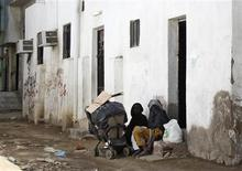 """Immigrant women sit on a doorstep in the Jeddah slum of Karantina, February 12, 2013. Jeddah has attracted outsiders for centuries, being the main port of arrival for Muslims making the haj pilgrimage to Mecca. It is this history that gives Karantina its name: older residents can remember when it was """"quarantine"""" for pilgrims. But the people who now live in this slum in the south of Saudi Arabia's second biggest city were drawn not only by religious devotion but also the top oil exporter's wealth. They live in a legal limbo, sometimes for generations. Picture taken February 12, 2013. To match Feature SAUDI-IMMIGRANTS/SLUM REUTERS/Susan Baaghil"""