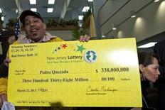 Pedro Quezada, winner of the Powerball lottery, holds up the promotional Powerball jackpot check of $338 million at the end of a news conference at the New Jersey Lottery headquarters in Trenton, March 26, 2013. REUTERS/Eduardo Munoz