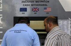 Les autorités chypriotes vont interdire pendant une semaine les encaissements de chèques et limiter à 3.000 euros la somme que les particuliers pourront emporter hors de l'île afin d'éviter une fuite des capitaux à la réouverture des banques, selon le quotidien grec Kathimerini. /Photo prise le 27 mars 2013/REUTERS/Yannis Behrakis
